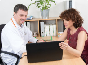 male doctor adult woman looking at the laptop